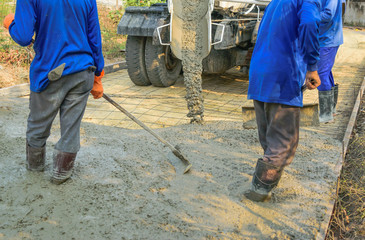Worker spreading concrete from the cement mixer