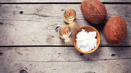 Coconuts and coconut oil on  vintage wooden background.