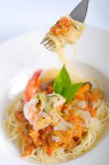 Shrimp spaghetti with tomato sauce on a fork.