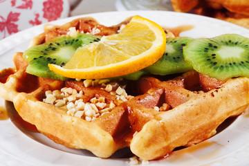 Belgian waffles with orange, kiwi, nuts on a plate close-up