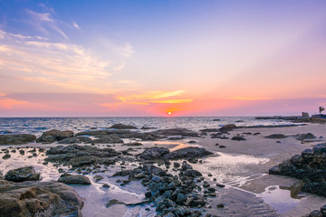 Sea , sand and rocks at the sunset.