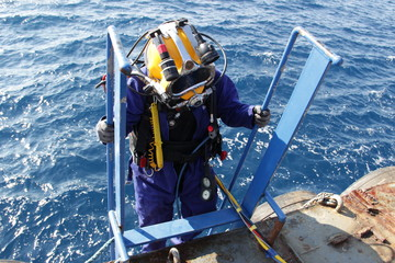 Photo of a diver in suit and helmet, which descends from the ship down to the water