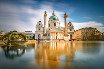 Spoed Fotobehang Wenen View on st. Charles's church on Karlsplatz in Vienna. Long exposure technic with blurred clouds and glossy water