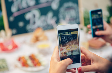 Woman hands taking photo to table with food