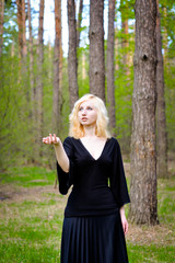 Beautiful smiling magic girl in the wood. Fashionable young short haired blond woman posing in the forest park wearing fancy empire style dress holding flowers. Concept of fantasy and magic.