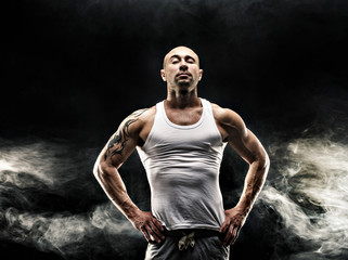 male in white tank top with strong muscles on the black background