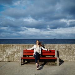 beautiful blonde woman sitting on bench