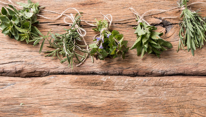 Herbs on wooden background. Mint, thyme, balm and other medicinal herbs