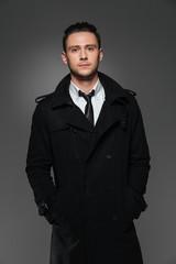 Portrait of confident handsome young businessman in black coat