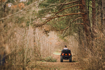 Happy beautiful couple driving four-wheelers ATV on forest road