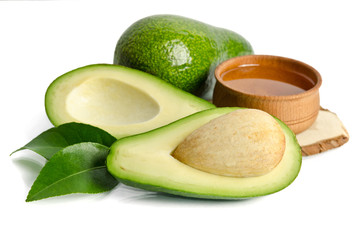 fresh avocado with avocado oil in the wooden bowl isolated on wh