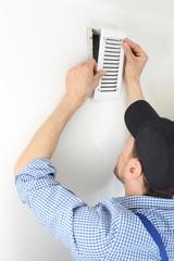 Handwerker öffnet Deckel eines Luftschachtes zum Filterwechsel.jpg