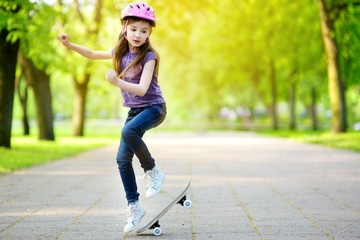 Pretty little girl learning to skateboard outdoors