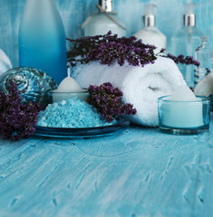 flowers lying on a blue wooden board with shell and candle Spa set