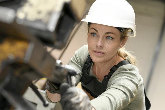 Woman with helmet working in metallurgy factory