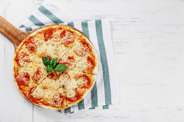 Hot true PEPPERONI ITALIAN PIZZA on towel with salami and cheese. TOP VIEW Tasty traditional pepperoni pizza on board on white wooden table. Copy space for your logo. Ideal for commercial