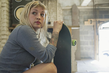 Young woman sitting with skateboard