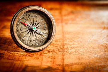 Fototapete - Vintage compass lies on an ancient world map.