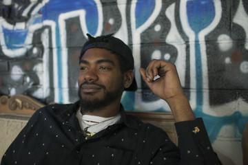 Young man sitting next to graffiti