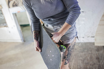 Young woman holding a skateboard.