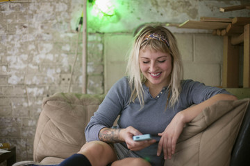 Young woman using smartphone while relaxing on sofa
