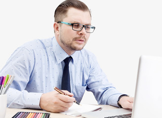 focused young designer in glasses at the laptop with notebook
