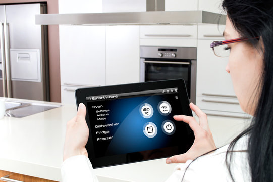 A woman turns on the oven by tablet's smarthome application.