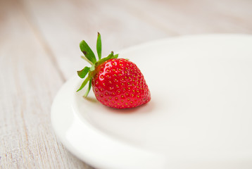 Ripe strawberry fruit on a white plate