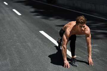 Sports. Healthy Athletic Man With Fit Muscular Body In Starting Position For Running On Road. Handsome Runner Ready To Start Sprint Race. Fitness Model Training Outdoors In Summer. Workout Concept