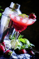 Alcoholic cocktail with strawberry, lime and ice in the glass, d