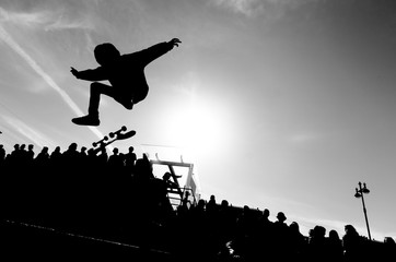 Man making trick by skateboard in the air. High jump by skate. Free space for a text. Extreme sport concept. Black and white picture.
