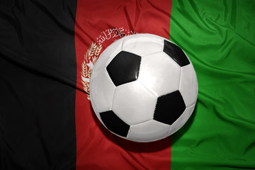 black and white football ball on the national flag of afghanistan