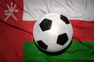 black and white football ball on the national flag of oman