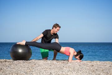 Sport und Fitness Instruktor zeigt junger Frau wie man mit Gymnastikball den Rücken trainiert am Strand im Freien