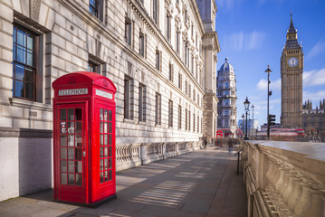 Traditional red british telephone box with Big Ben and Double Decker bus at the background on a sunny afternoon with blue sky and clouds - London, UK