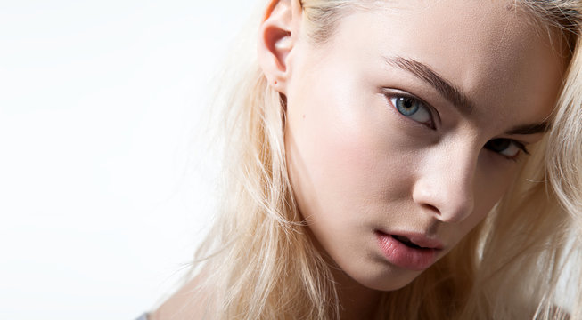 Closeup of a blue-eyed face fashion model with beautiful eyebrows on a white background