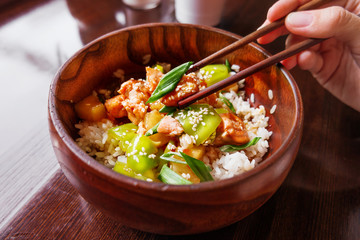 Asian cuisine - rice in sauce with stir fried vegetables, pineapple and salmon. Wooden bowl with chopsticks.