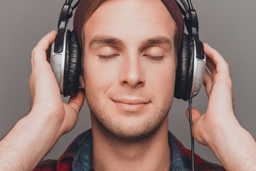 Close up portrait of relaxed man in head-phones listening music