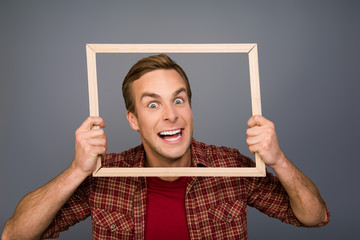 Handsome creative man grimacing inside frame