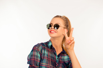 cute girl in a checkered shirt with sunglasses showing two finge