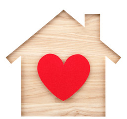 House shaped paper cutout and heart on natural wood lumber.