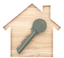 House and key shaped paper cutout on natural wood lumber.