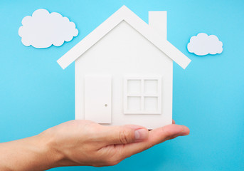 Hand holding house against sky made of paper.