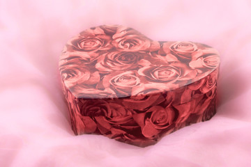 Box with roses on delicate pink fluffy background Valentine's Day
