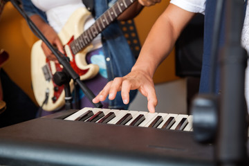 Man's Hand Playing Piano In Recording Studio