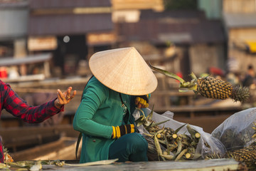 Vietnamese woman with typical conical hat ( sugegasa),  cut pineapple fruits in the  Cai Rang floating market on the Mekong delta. Can Tho, Vietnam