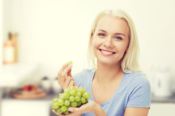 happy woman eating grapes on kitchen Fototapete
