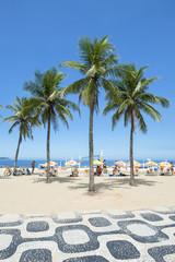 Classic view of Ipanema Beach Rio de Janeiro boardwalk with palm trees and blue sky