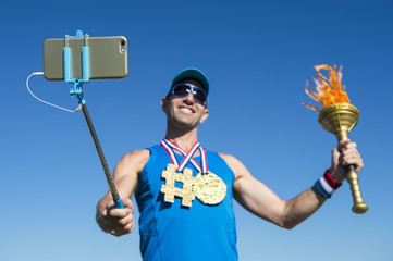 Athlete smiling for a selfie with a gold hashtag medal and a sport torch against bright blue sky