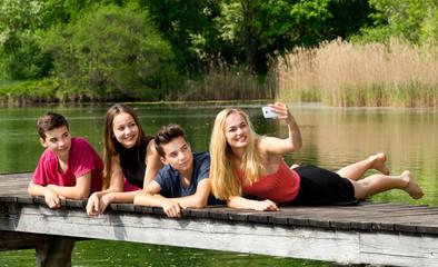 Jugendliche / Teenager machen ein Selfie draußen am See